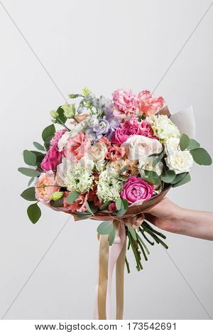 Rich bunch of pink eustoma and roses flowers, green leaf in hand Fresh spring bouquet. Summer Background.