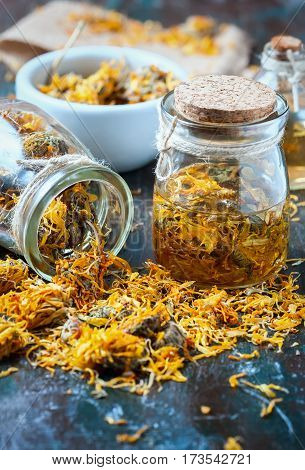 Bottles And Dried Calendula Officinalis Petals With Macerated Oil On Wooden Background.