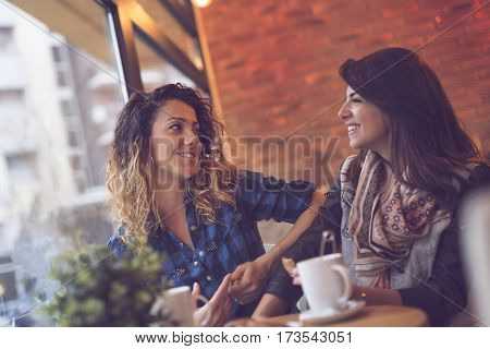Two beautiful young women sitting in a cafe drinking coffee and having a pleasant conversation. Focus on the girl on the left