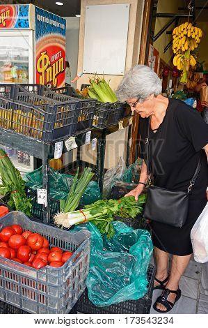 HERAKLION, CRETE - SEPTEMBER 19, 2016 - Customer choosing fruit and vegetables at a city centre shop along Odos 1821 Heraklion Crete Greece Europe, September 19, 2016.
