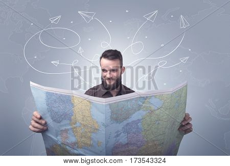 Handsome young man holding a map with drawn paper planes flying behind him