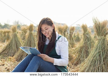 young pretty chinese woman sits in golden cereal field