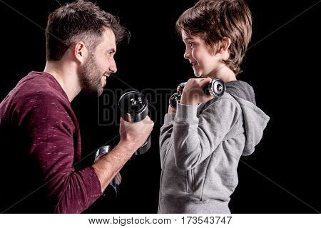 Side view of father and son training with dumbbells and looking at each other