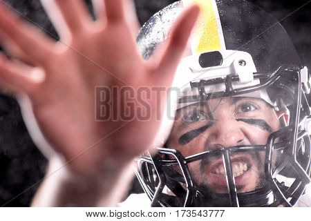 Close-up view aggressive man in helmet playing american football on black