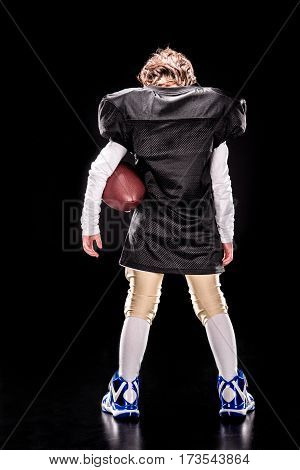 Back view of little boy american football player standing with ball on black
