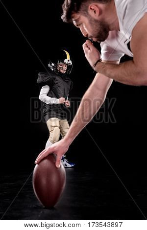 Trainer holding rugby ball and boy preparing to play american football