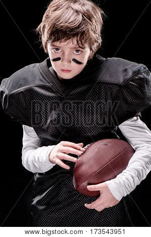 Serious little boy american football player holding rugby ball and looking at camera