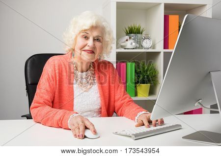 Working grandma at the office sitting by the computer