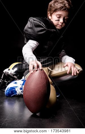 Cute little boy american football player crouching and playing with ball