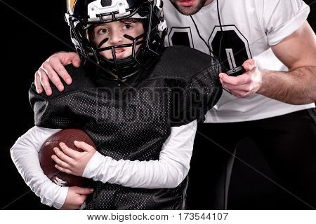Cropped shot of boy and trainer playing american football on black