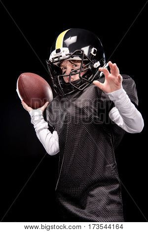 Angry little boy in uniform playing american football on black