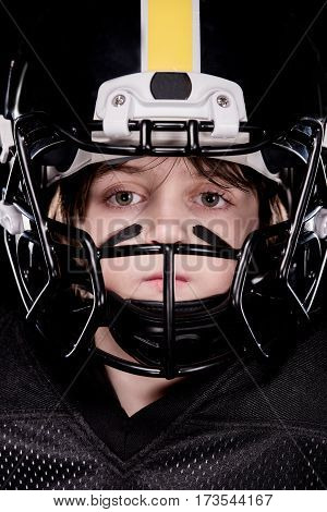 Close-up view of boy american football player in helmet looking at camera