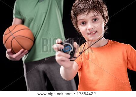 boy showing stopwatch with man holding basketball ball on background on black