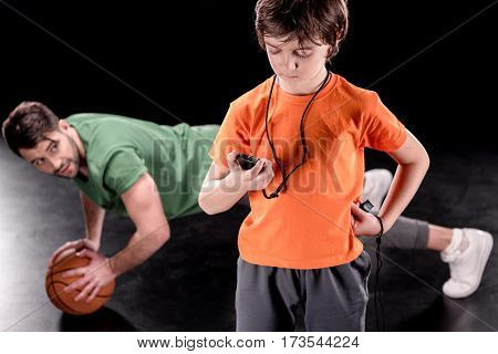 concentrated boy with stopwatch controlling time while man training with ball on black