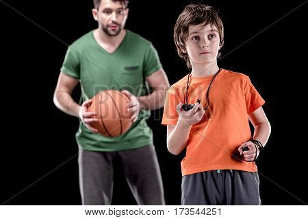 boy with stopwatch controlling time with man holding basketball ball on black focus on foreground