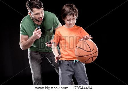 man controlling time while concentrated boy training with basketball ball on black