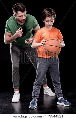 man controlling time while boy training with basketball ball on black