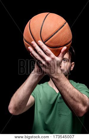 close up view of man going to throw basketball ball on black