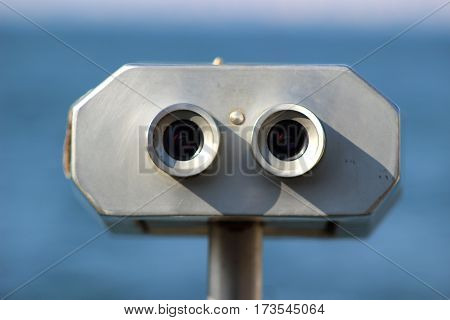 A public binocular machine sits at the shore for better viewing