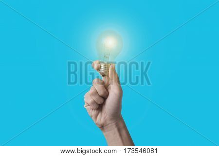 Business hand holding light bulb on blue background. concept of new ideas with innovation and creativity.