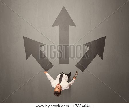 Young contemplating businessman stands in front of brown arrows