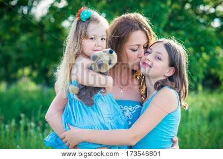 portrait of mother and two daughters. mother kissing daughter