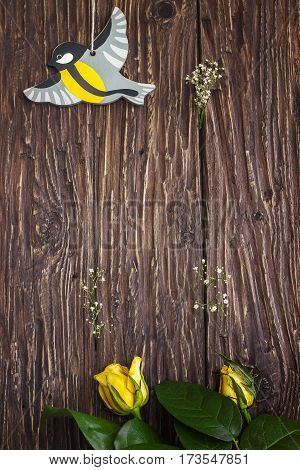 Bird toy and yellow roses on old wooden background with wood copy space