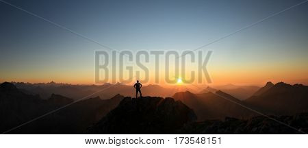 Happy winning success man at sunset or sunrise standing relaxed and is happy for having reached mountain top summit goal during hiking travel trek. Tirol, Austria. Bavaria.