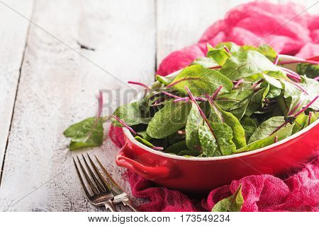 Fresh chard leaves in a bowl on white wooden background