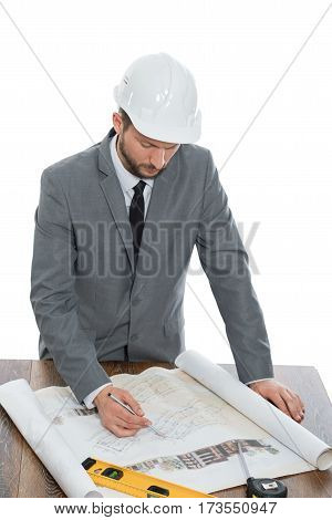 Working hard. Vertical studio shot of a professional architect drawing up plans isolated on white construction business building developing development planning project profession occupation concept