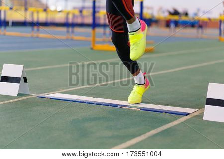Sportsman landing his leg on board before taking off in long jump or tripple jump competition