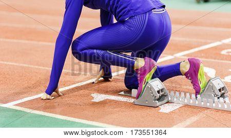 Sportswoman at the starting blocks before sprint running event