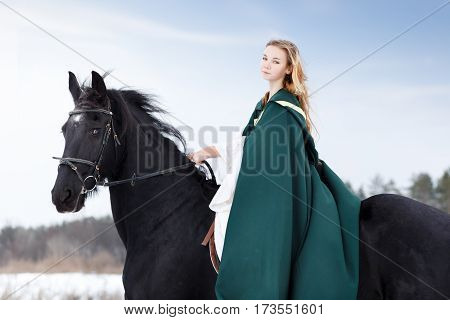 Young girl in white dress and green cape riding black thoroughbred horse in winter. Historical image