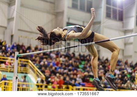 Young professional sportswoman jumping over bar in high jump competition against crowded grandstand.