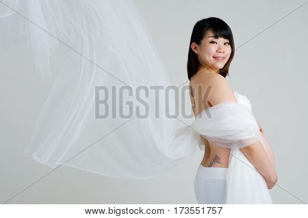 Indoor portrait of a cheerful asian pregnant woman