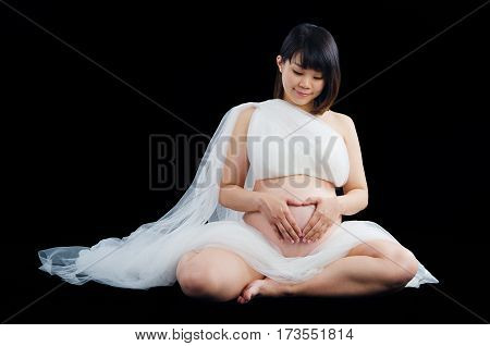 Asian pregnant woman sitting on the floor looking at her belly
