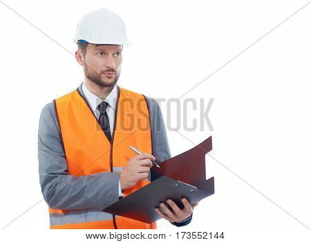 Confident constructionist. Confident male constructionist looking away while making notes on his clipboard copyspace isolated hardhat safety vest wearing occupation building project architectural
