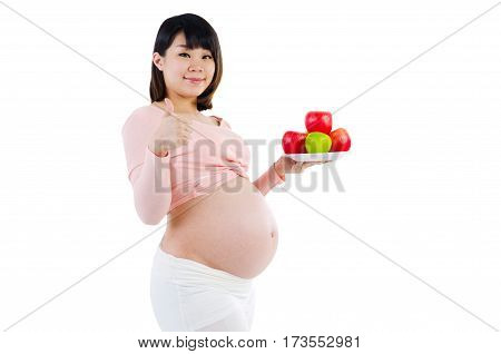 Asian pregnant woman holding a plate of apple