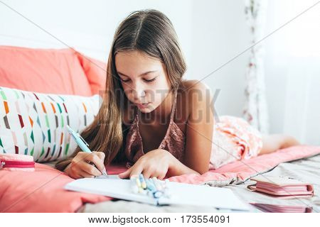 10-12 years old pre teen girl writing diary in pink bedroom