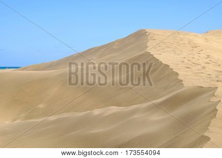 Sand dunes in Maspalomas and blue sky on the Canary island Gran Canaria Spain.