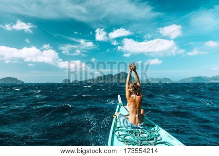 Back view of the young woman relaxing on the boat and looking at the island. Travelling tour in Asia: El Nido, Palawan, Philippines.