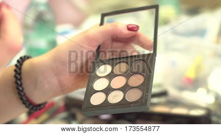 Make-up artist taking eye shadows from multicolor make-up eyeshadows palette in beauty salon. Closeup of colourful professional set of eye shadows