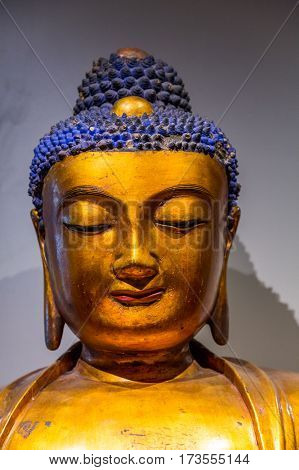 Golden buddha statue against a white wall