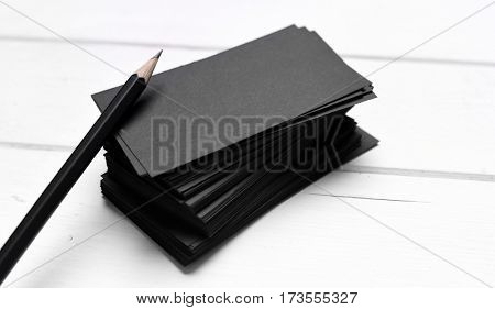 black business cards with pencil on a white table