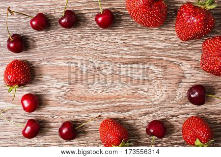 Ripe juicy red cherry and a big red strawberry lying on a wooden background. Sweet summer berries. Flat lay. top view. Frame from berries copyspace.