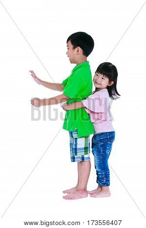 Asian sister and hugging his brother smiling happily, isolated on white background. Concept about loving and bonding of sibling. Playful boy driving a train or car. Children role playing. Studio shot.