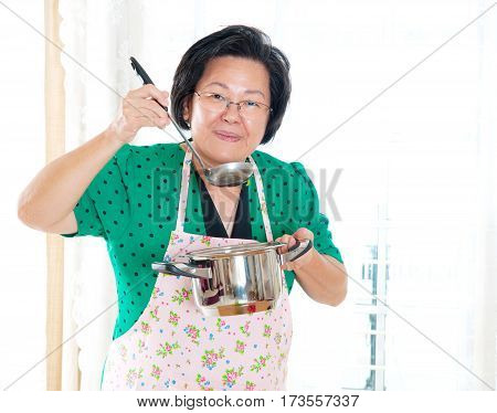 Asian senior woman tasting her own cooking