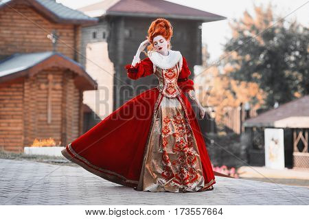 Red Queen in the castle. Red-haired woman lady in a chic vintage dress. Fashion lady Photo. Lady in red dress