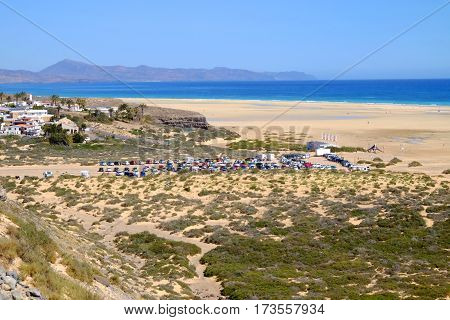 View on the famous beach Playa de Sotavento with yellow sand beautiful water colors of the ocean and mountains on the Canary Island Fuerteventura Spain - 16.02.2017.