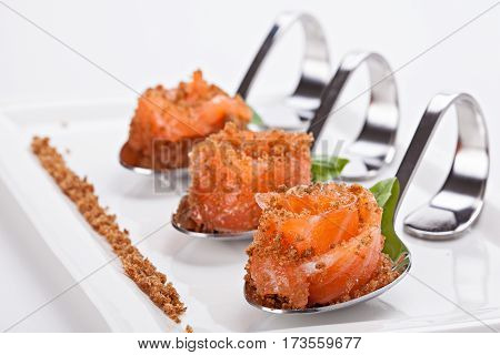 Gourmet appetizer of salmon served in a special decorative spoons. Close up.